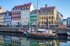 o barco e as construções coloridas bonitas refletiram na água calma do porto, Copenhaga, Dinamarca Imagem de Stock
