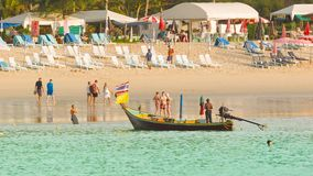 O barco e os turistas de madeira longos tradicionais de motor andam em uma praia de Kamala no tempo da maré baixa com praia Fotos de Stock