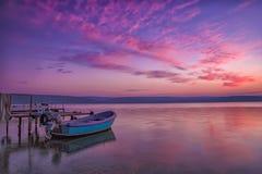 O barco em um cais após o por do sol Fotografia de Stock