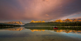 O barco em um lago como a luz da manhã bate as partes superiores da montanha alta Foto de Stock