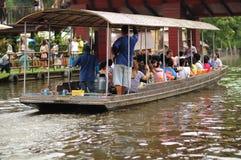 O barco está navegando no canal com completamente dos povos no mercado do flutuador, vagabundos Imagem de Stock