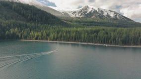O barco está navegando por um lago de montanha Drone cinemático sobrevoando um lago nas montanhas video estoque