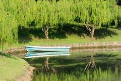 O barco estacionou em um rio perto de uma floresta verde imagem de stock