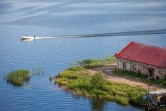 O barco flutua no lago Celeiro velho do tijolo imagens de stock