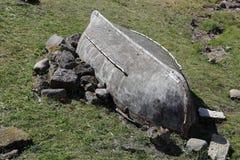O barco invertido velho encontra-se entre pedras Fotos de Stock