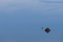 O barco, o pescador e a luz solar na costa equipam a pesca na noite, reflexão do céu azul na água Praia no verão Fotografia de Stock