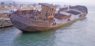 O barco oxidado velho está no cais no banco de rio imagem de stock royalty free