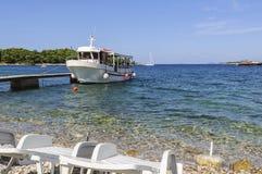 O barco para o transporte dos turistas, viajantes e passageiros dos veraneantes, amarrados ao cais Mar de adriático, Croatia imagens de stock royalty free