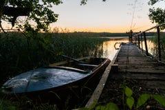 O barco velho no cais no por do sol Na distância uma pode ver a silhueta de um pescador Imagens de Stock Royalty Free