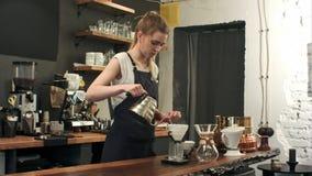 O barista fêmea novo na cafetaria moderna na moda do café derrama a água a ferver sobre as terras de café que fazem um derramamen Fotos de Stock Royalty Free