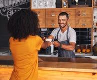 O barista masculino oferece o café quente ao cliente fêmea fotografia de stock