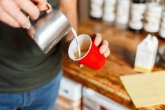 O barista profissional faz o café em sua cafetaria do vintage O homem derrama o café de um copo do metal em um copo vermelho Clos imagens de stock