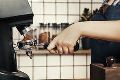 O barista profissional mói o café em uma cafetaria do escandinavo-estilo fotos de stock