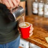 O barista profissional novo derrama o creme de um copo do metal em um latte delicioso quente O homem faz o café Close-up fotografia de stock royalty free