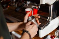 O barista profissional novo prepara o café delicioso em uma máquina moderna do café O homem derrama o café em uma caneca do metal fotografia de stock