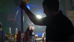 O Barkeeper atrás do suporte da barra derrama um álcool doce de uma garrafa no vidro no clube noturno video estoque
