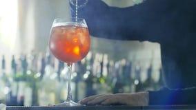 O Barkeeper com a colher longa do metal faz à disposição o cocktail brilhante com cubos e licor de gelo no vidro na tabela filme