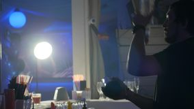 O Barkeeper faz um truque com um abanador e uma garrafa de vidro perto do contador da barra vídeos de arquivo