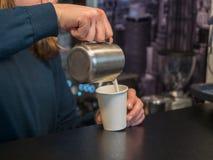 O barman derrama o café no vidro branco do papper Foto atrás do contador da barra com fundo e delicado borrados imagens de stock