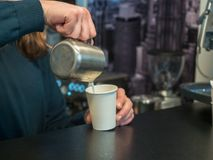 O barman derrama o café no vidro de papel Foto atrás do contador da barra com fundo borrado e foco macio fotos de stock royalty free