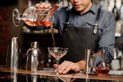 O barman derrama o cocktail doce em bocal fotos de stock