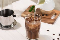 O barman derrama o leite no vidro do café imagens de stock