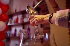 O barman derrama o suco de fruta mixa no vidro de vinho fotos de stock royalty free