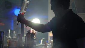 O barman derrama um licor doce de uma garrafa no vidro atrás do suporte da barra no clube noturno filme
