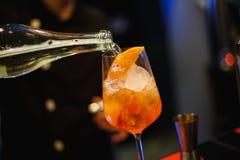 O barman derrama um vidro do álcool fotografia de stock