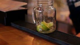 O barman espreme o suco de lima com a colher, cozinhando Mojito no close-up da barra filme