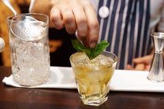 O barman está adicionando a hortelã ao cocktail Imagem de Stock Royalty Free