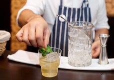 O barman está adicionando a hortelã ao cocktail Imagens de Stock Royalty Free