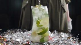 O barman está agitando cocktail na barra Fim acima Empregado de bar fêmea que usa a colher que agita o cocktail congelado em um v vídeos de arquivo