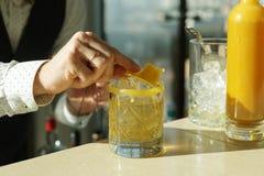 O barman está decorando uma bebida com cera Fotografia de Stock Royalty Free