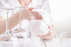 O barman fêmea limpa os vidros de vinho O garçom limpa os wi Imagem de Stock Royalty Free