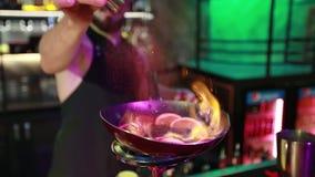 O barman farpado derrama a canela em uma bandeja com laranjas em um queimador de gás filme