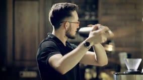 O barman farpado na moda vestido no uniforme preto está agitando a garrafa que prepara bebidas no clube noturno O homem à moda é video estoque