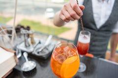 O barman faz o cocktail Aperol spritz Vidro de Misted, foco seletivo Bebida alcoólica baseada no contador da barra com gelo imagens de stock royalty free