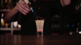 O barman faz um cocktail do fogo Cocktail de Hiroshima O empregado de bar inflama o isqueiro na barra video estoque