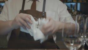 O barman irreconhecível no avental limpa um vidro de vinho com uma toalha Muitos vidros do vidro estão na barra Prepara??o para filme