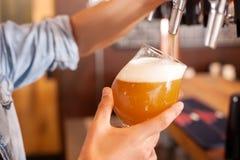 O barman novo alegre está derramando a cerveja pilsen no bar Imagem de Stock Royalty Free