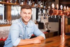 O barman novo alegre está esperando o cliente Imagens de Stock Royalty Free