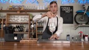 O barman põe os cubos de gelo em um vidro Um barman gerencie o gelo no vidro com a colher da barra vídeos de arquivo