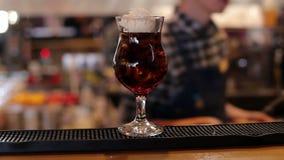O barman põe uma bola do gelado sobre um cocktail com cola e gelo, close-up filme