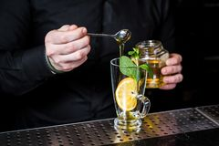 O barman prepara o chá do fruto com arandos em um fundo de vidro, escuro imagem de stock