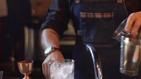 O barman prepara o coctail alcoólico na barra moderna Adicionando o gelo em agitar a garrafa filme