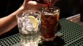 O barman prepara um cocktail com cola vídeos de arquivo