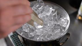 O barman retira os cubos de gelo para um cocktail, usando o fórceps Cubeta de gelo do metal filme