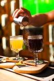 O barman termina a preparação do cocktail ferventado com especiarias do vinho no cristal adicionando um amargo do açúcar pulveriz fotografia de stock royalty free