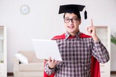 O barrete vestindo do estudante do super-herói e guardar um portátil Imagens de Stock